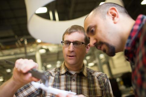 professor and student looking at tools